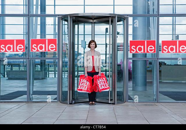 Woman in shop doorway with sale bags - Stock Image