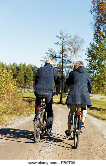 Sweden, Sodermanland, Rear view of man and woman cycling - Stock Image
