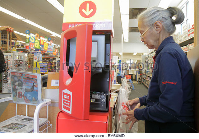 Miami Beach Florida CVS Pharmacy drug store senior Hispanic woman employee replaces printing paper roll coupon dispenser - Stock Image