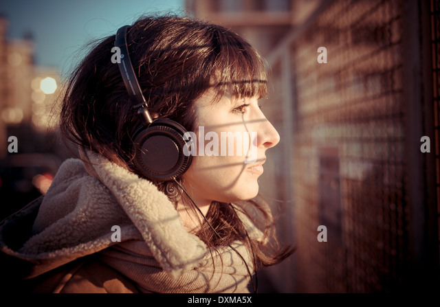beautiful young woman listening to music headphones in the city winter - Stock-Bilder
