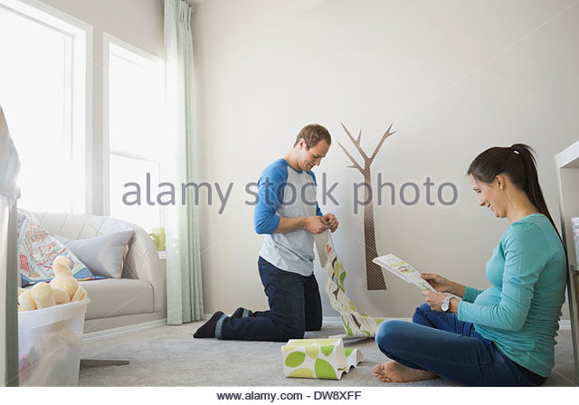 Expectant couple decorating nursery - Stock Image