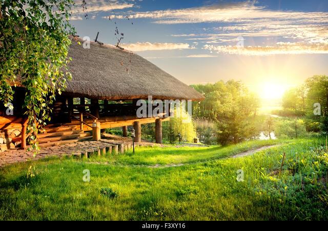 House of log near lake at sunset - Stock Image