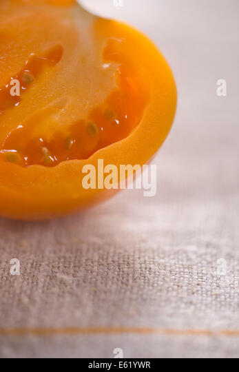 Half an orange tomato on rustic linen. Juice and seeds visible. Bright, summery setting. - Stock Image