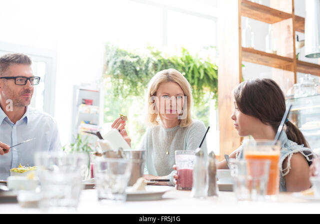 Family eating lunch at cafe table - Stock Image