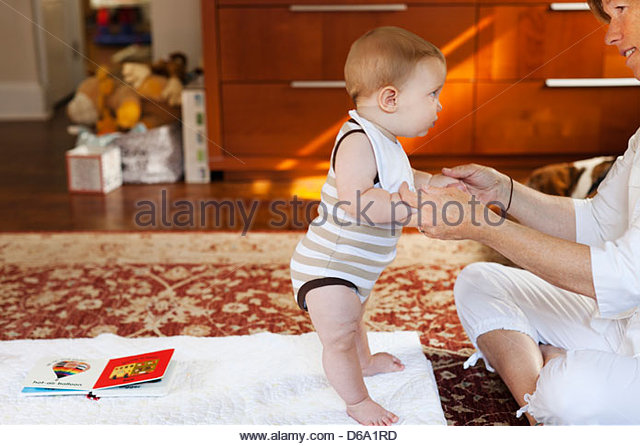 Mother and baby son playing on carpet - Stock-Bilder