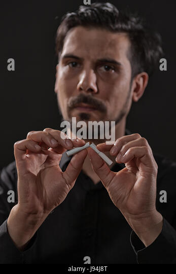 Portrait of adult man who is decided to quit smoking. - Stock Image