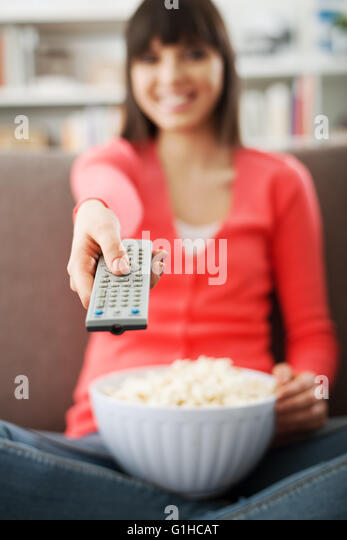 Young smiling woman at home sitting on the couch and watching tv, she is holding a remote control and eating popcorn - Stock Image