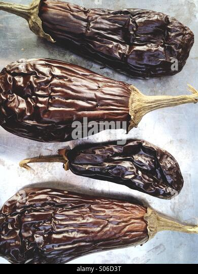 Grilled eggplant (also known as aubergine) on a baking tray after being cooked whole. - Stock Image
