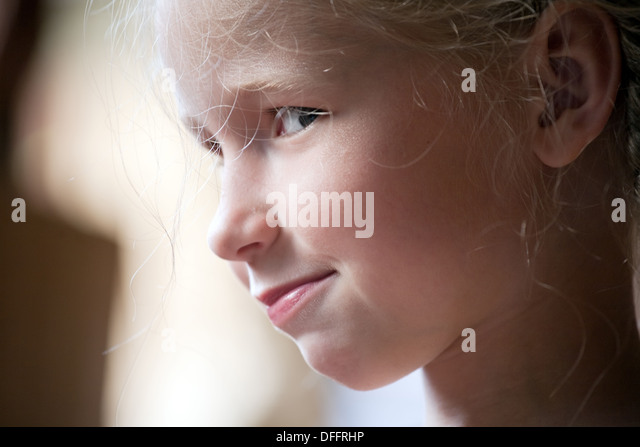 playful cunning smiling girl portrait closeup - Stock Image