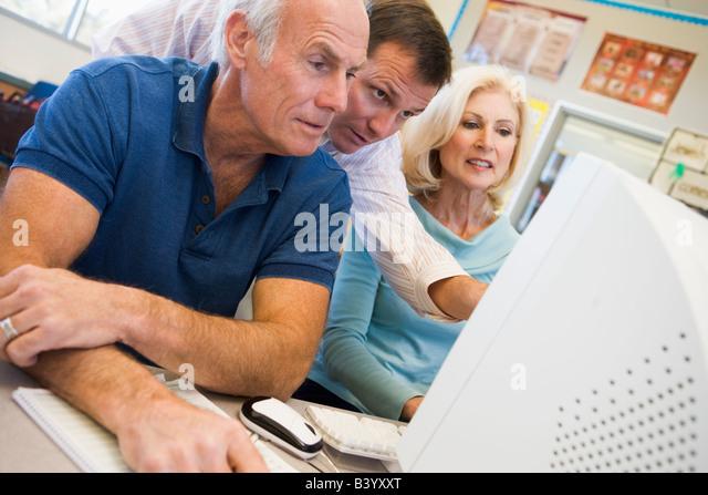 Three people at computer terminal - Stock Image
