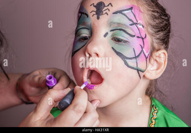 Make-up artist working with a little girl before halloween party. She is applying purple lip gloss - Stock Image