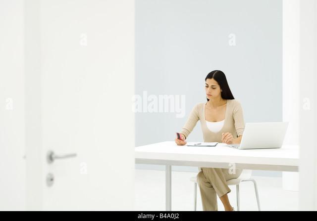 Businesswoman working alone in empty office - Stock-Bilder