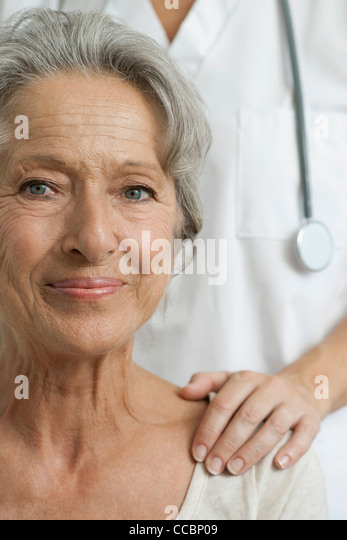 Senior woman with caring doctor, cropped - Stock Image