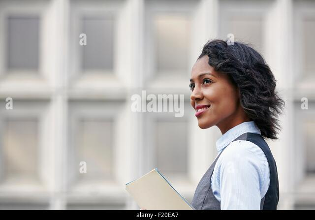 Portrait of young business woman holding paper work, looking away, smiling, side view - Stock Image