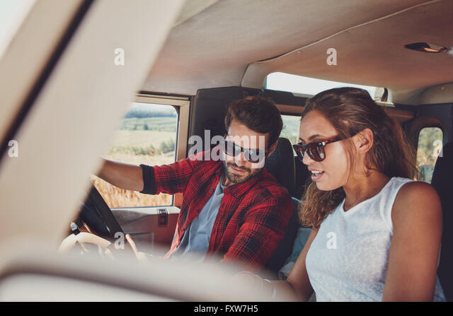 Young couple sitting inside their car and looking at something interesting. Young man and woman sitting together - Stock Image
