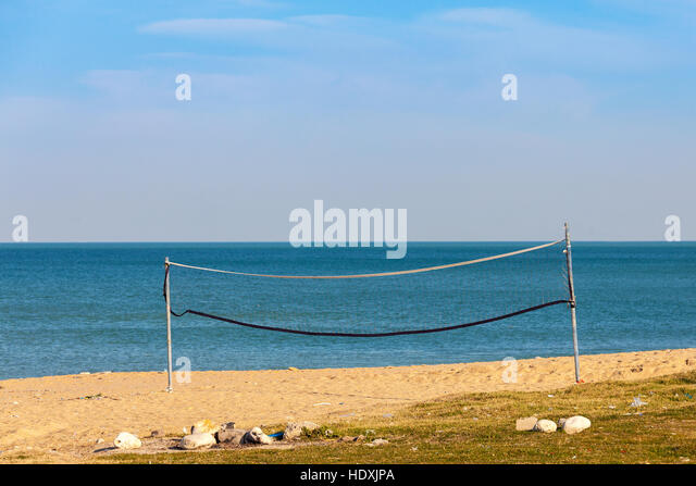 Old and neglected volleyball net on the beach. - Stock Image