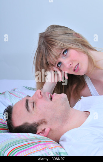 Couple in bed, woman frustrated while her partner snores - Stock Image