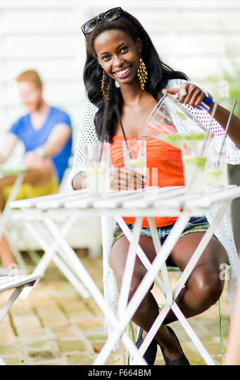 Attractive black woman sitting at a cafe table outdoors and drinking a refreshing beverage during a hot summer day - Stock Image