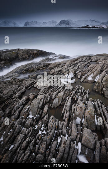 Icy and rocky stream running into the sea. - Stock Image