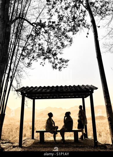 Tourists having a rest under a sun shelter at the Thailand to Burma Death Railway. Kanchanaburi Thailand. - Stock Image