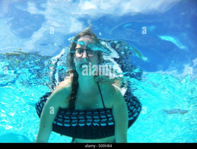 Woman in inner tube underwater - Stock Image