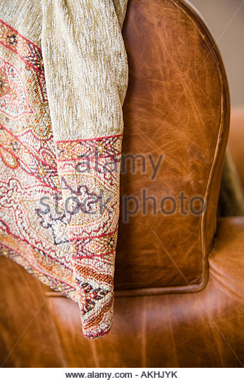 Detail of leather couch arm with throw blanket. - Stock Image