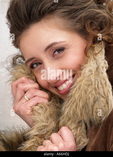 Portrait of brown haired girl woman smiling into the camera holding fake fur coat collar - Stock Image