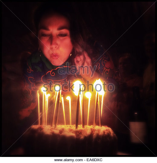 Girl blowing out birthday candles on cake - Stock Image