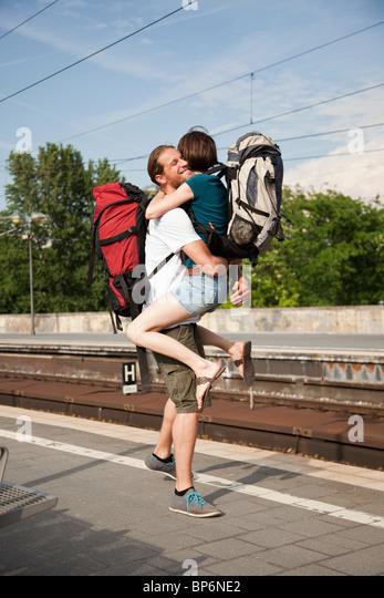 An ecstatic woman hugs her boyfriend on a train platform - Stock Image