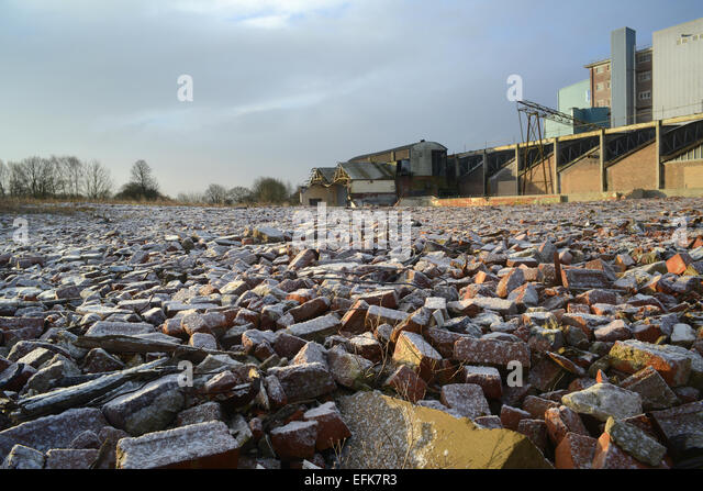 piles of rubble on derelict land and factory building covered by winter snow near selby yorkshire united kingdom - Stock Image