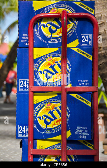 Stacked cases of Carib beer on red dolly cart, St Maarten - Stock Image