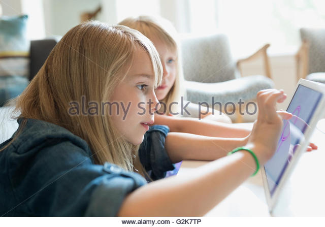 Sisters drawing with digital tablet in living room - Stock-Bilder