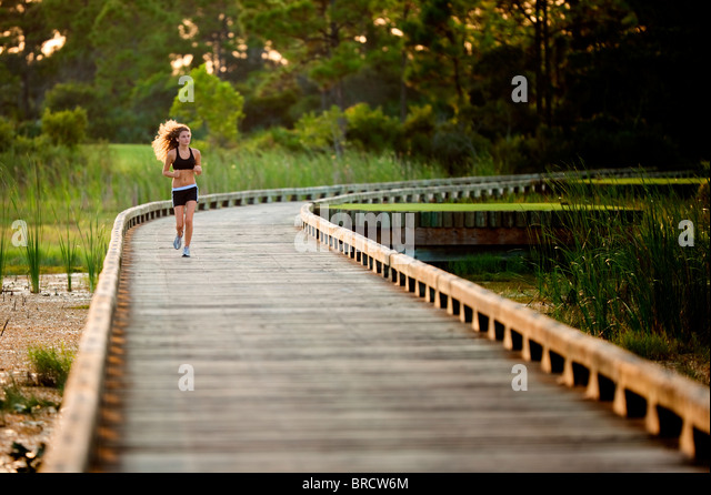 Running girl on a wooden bridge - Stock Image