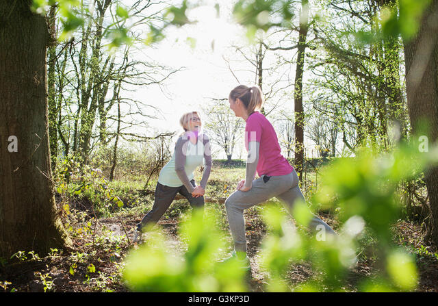 Women face to face in forest hands on knee lunging - Stock Image
