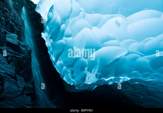 A waterfall trickles its way down the rock face of an ice cave inside the Mendenhall Glacier, Juneau, Alaska - Stock Image