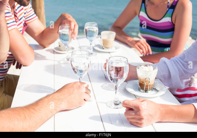 Group of friends relaxing in beach bar - Stock Image