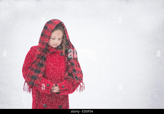 Girl (8-9) in red coat in snow - Stock Image