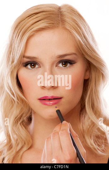 woman applying lip liner with a pencil - Stock Image