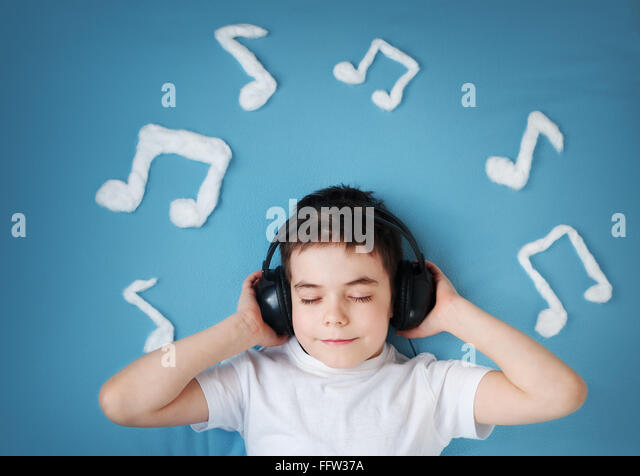 boy on blue blanket background with headphones - Stock-Bilder