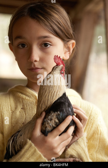 Girl holding her chicken at her farm - Stock Image