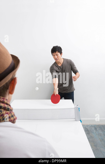 Mid adult man playing table tennis with friend - Stock Image
