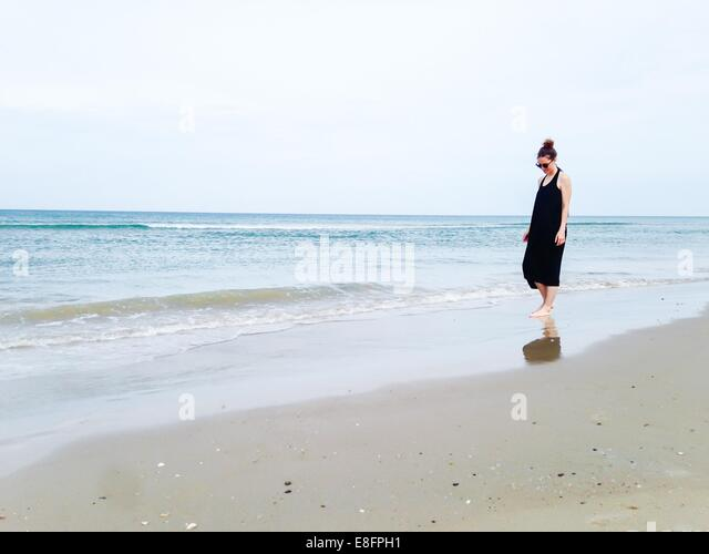 Woman walking along beach - Stock Image