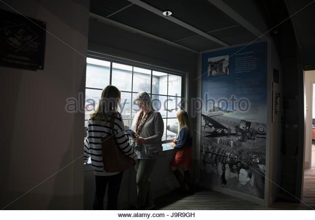 Female multi-generation family looking at exhibit in war museum - Stock-Bilder