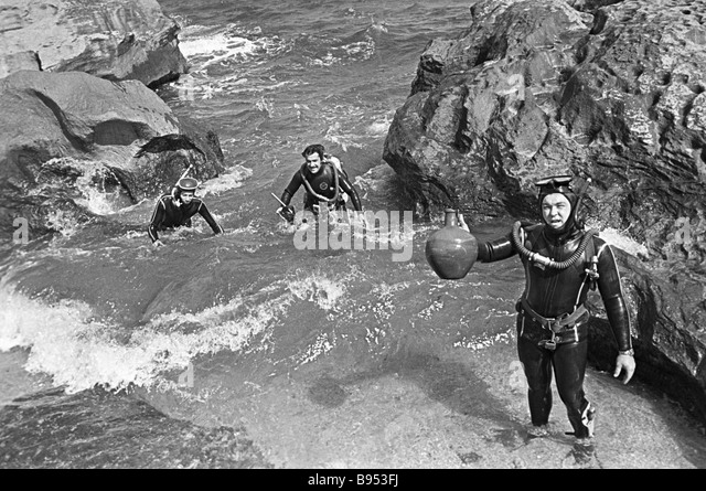 Aquanauts archaeologists surfacing antique objects - Stock Image