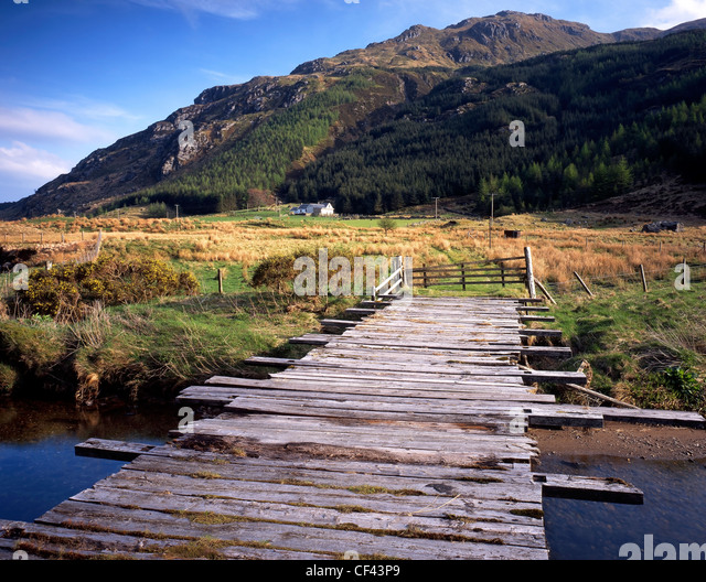 A wooden sheep bridge spans the River Massan in the heart of remote Glen Massan. - Stock Image