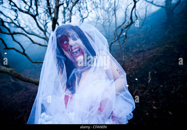 A young woman in full make-up taking part in a Zombie bride 'trash the wedding dress' - Stock Image
