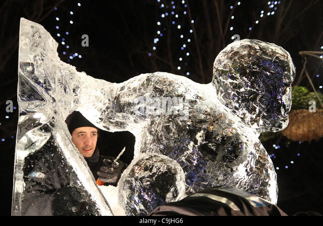 The Portuguese team composed of Pedro Mira & Niall Magee chisel on their  ice sculpture at the  4th annual London - Stock Image