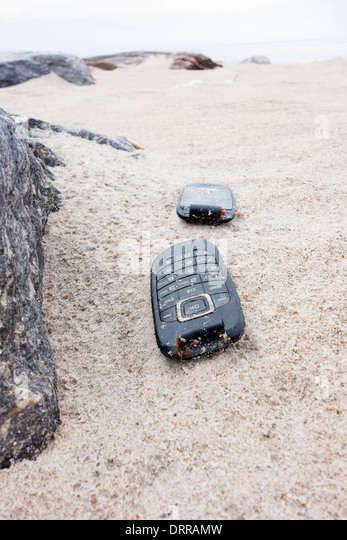USA, New York, Brooklyn, Coney Island: Damaged mobile phone lying on a sandy beach - Stock Image