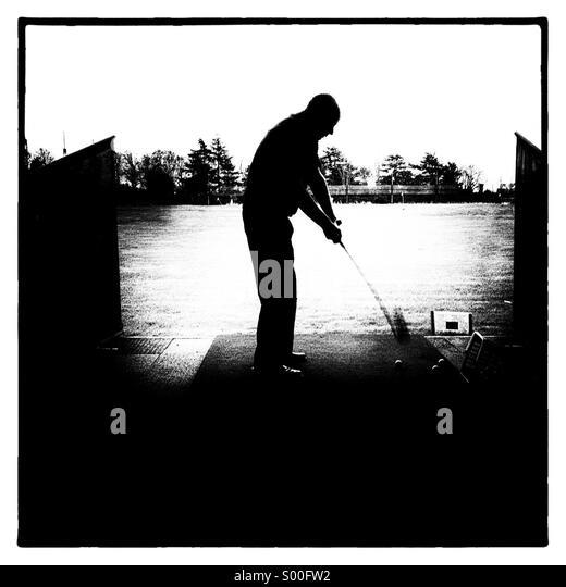 Golfer practising golf at driving  range - Stock Image