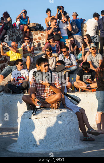 A crowd of people sitting waiting to see the Sunset, Oia, Santorini (Thera), Greece - Stock Image